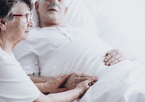 Woman holding man's hand in hospital bed