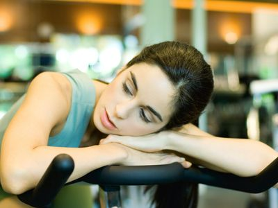 Woman on exercise bike, tired