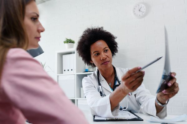 Doctor talking with patient at desk in medical office - stock photo