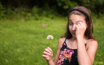 A young brunette girl holding a dandelion and rubbing her eyes.