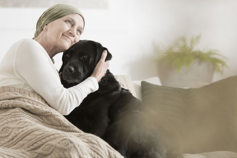 Cancer patient cuddles with dog
