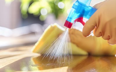 Close up of a gloved hand spraying a bottle of cleaner.