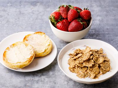 Bowl of bran cereal with strawberries and english muffins