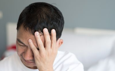 A man places his hand over the left side of his face. He appears to be in pain.