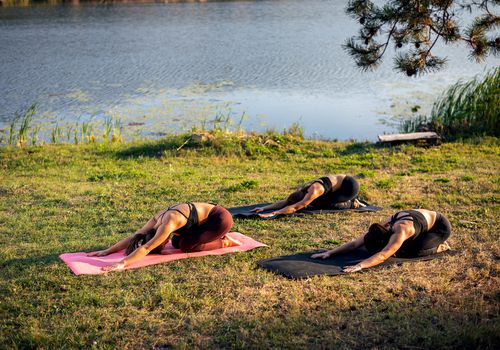 Women doing yoga on the lake