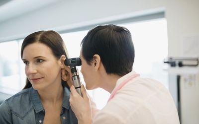 doctor examining woman's ear
