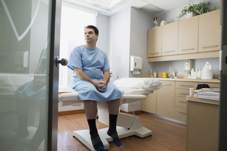Patient in hospital gown waiting in examination room