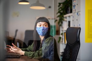An asian woman wearing a mask in an office.