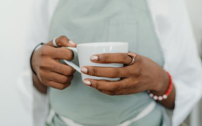 Close up of a Black person's hands holding a white coffee cup.