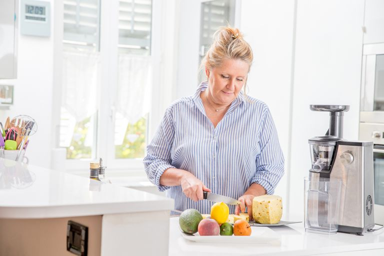 Woman slicing a pineapple for a juicer in her kitchen