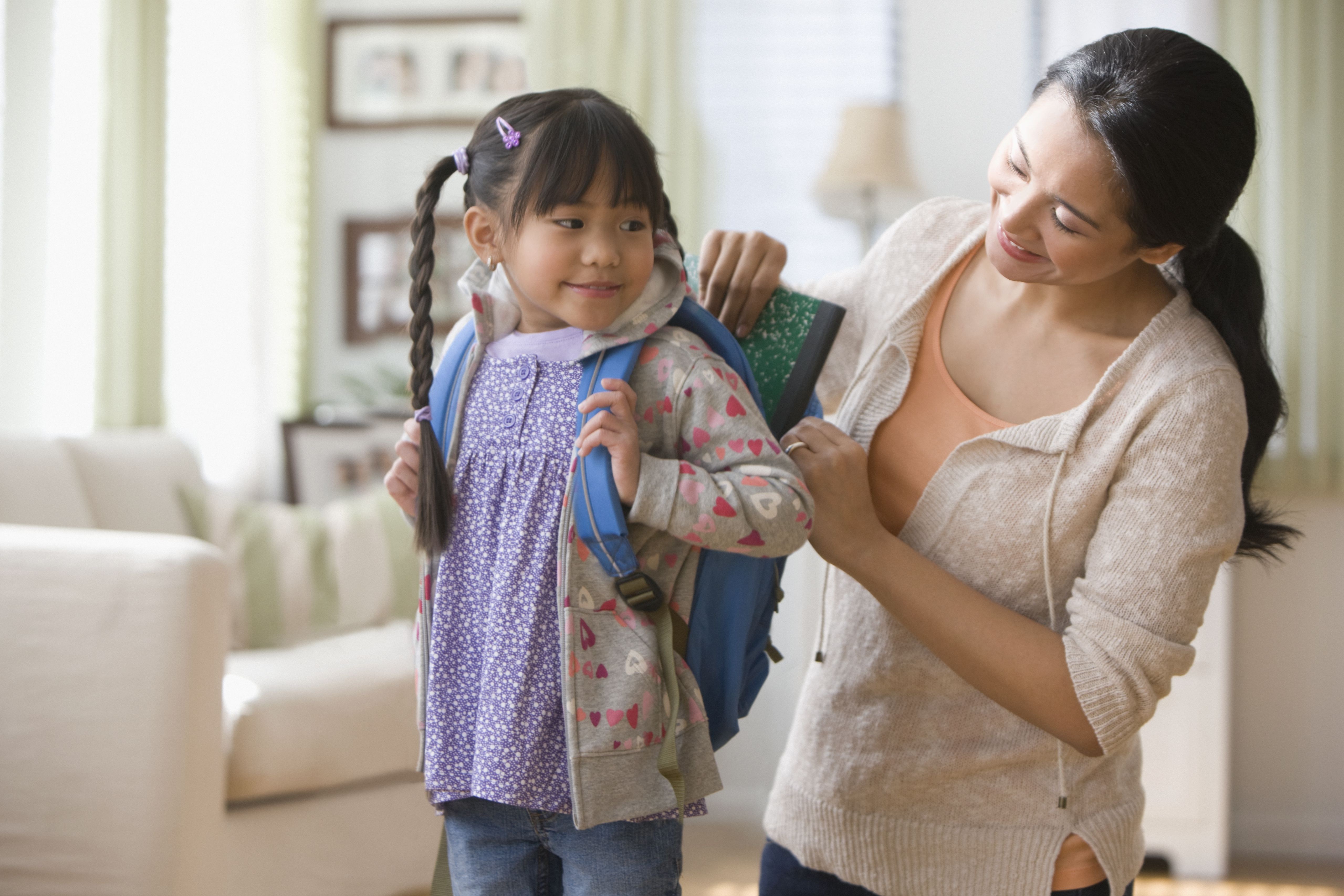 Asian mother helping daughter get ready for school