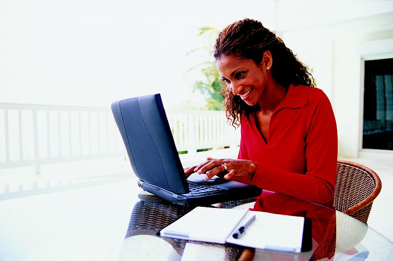 Woman using a laptop on outdoor deck