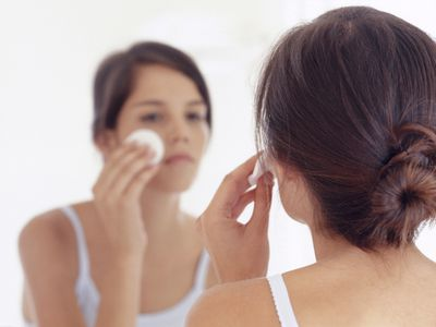 Woman using acne cleaning pad to wash face