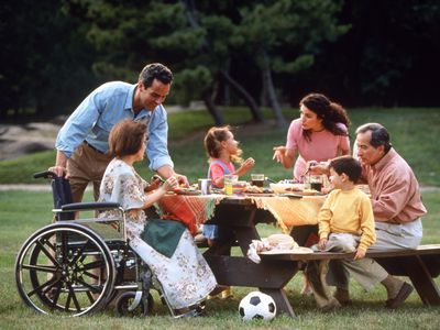 A woman in a wheelchair enjoying a picnic with her family
