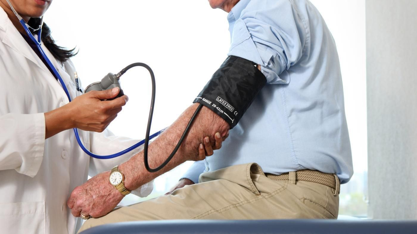 Man getting his blood pressure checked by doctor