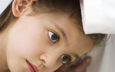 Doctor putting drops in little girl's ear