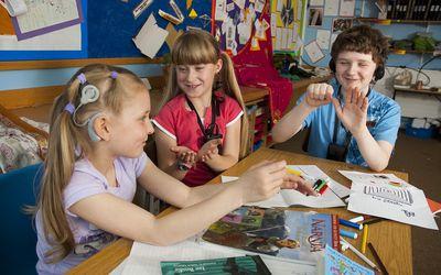 Deaf School children sign to each other in school class room