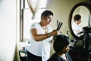Salon owner straightening client's hair in salon