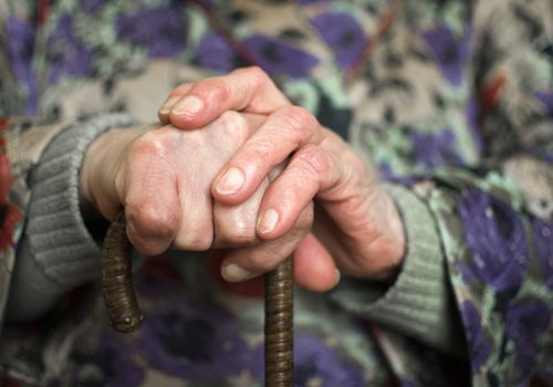 An older person's hand holding a cane.