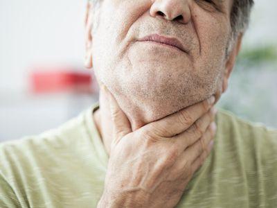 Older man feeling his throat