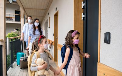 Family entering a hotel wearing face masks.