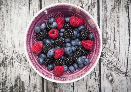 Bowl of different wild berries on wood