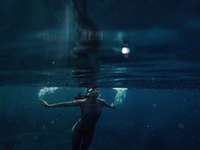 Woman with goggles swimming below the surface in dark water