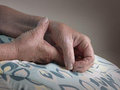 an elderly woman holding her wrist