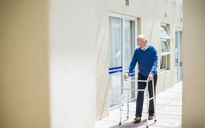 Senior man using walker on sidewalk