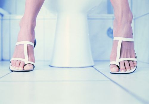 woman's feet next to toilet in bathroom