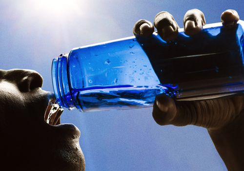 man drinking water from blue container
