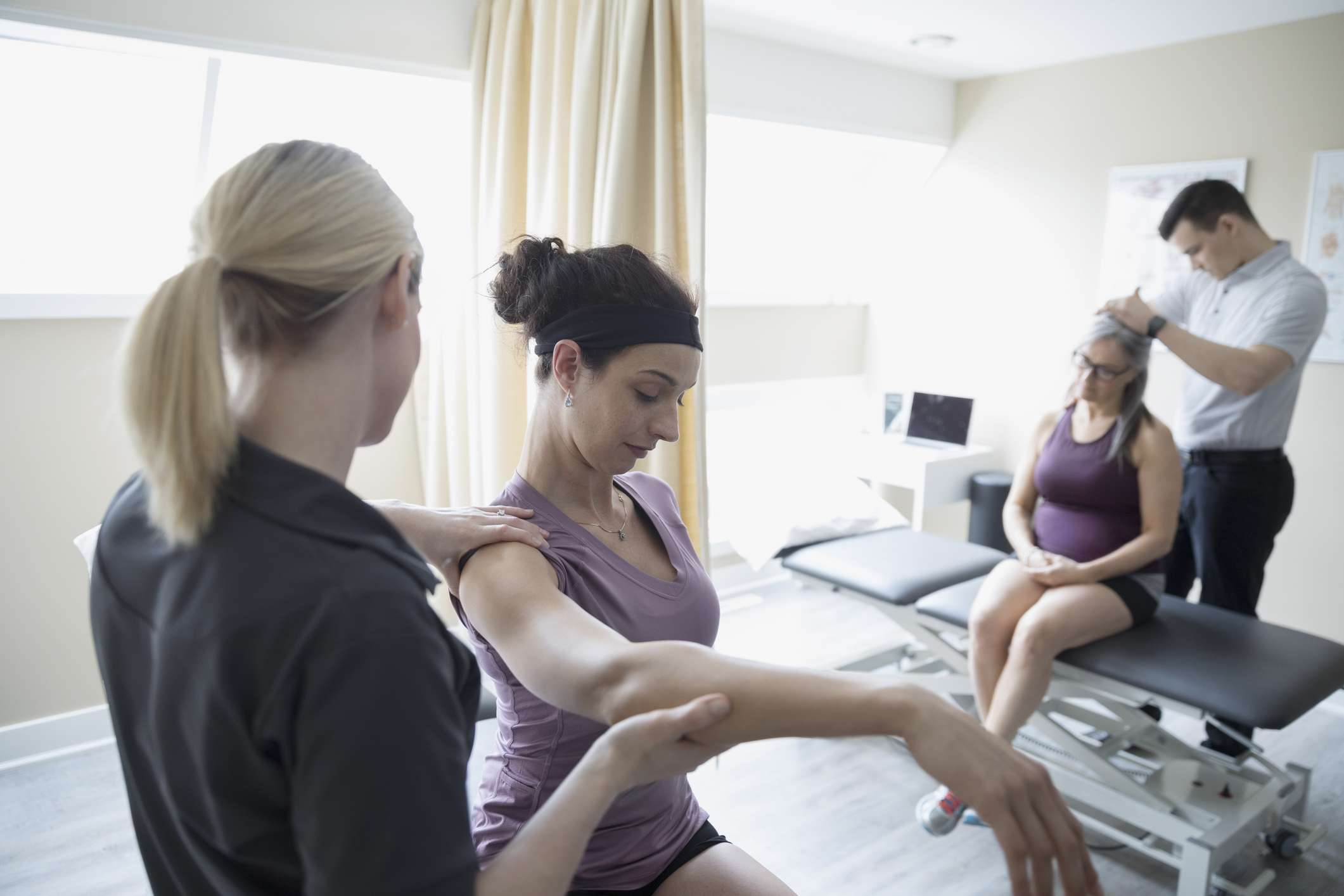 Photo of physical therapists examining patients.