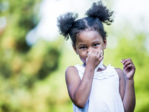 Child with dark skin and dark hair in pigtails stands outside, blowing their nose