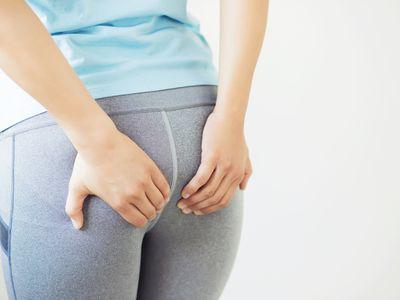 woman holding her butt