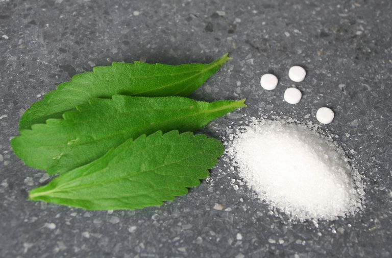 Stevia leaves with pile of sugar