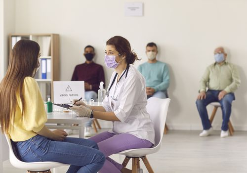 person at vaccination site sitting with nurse while others wait