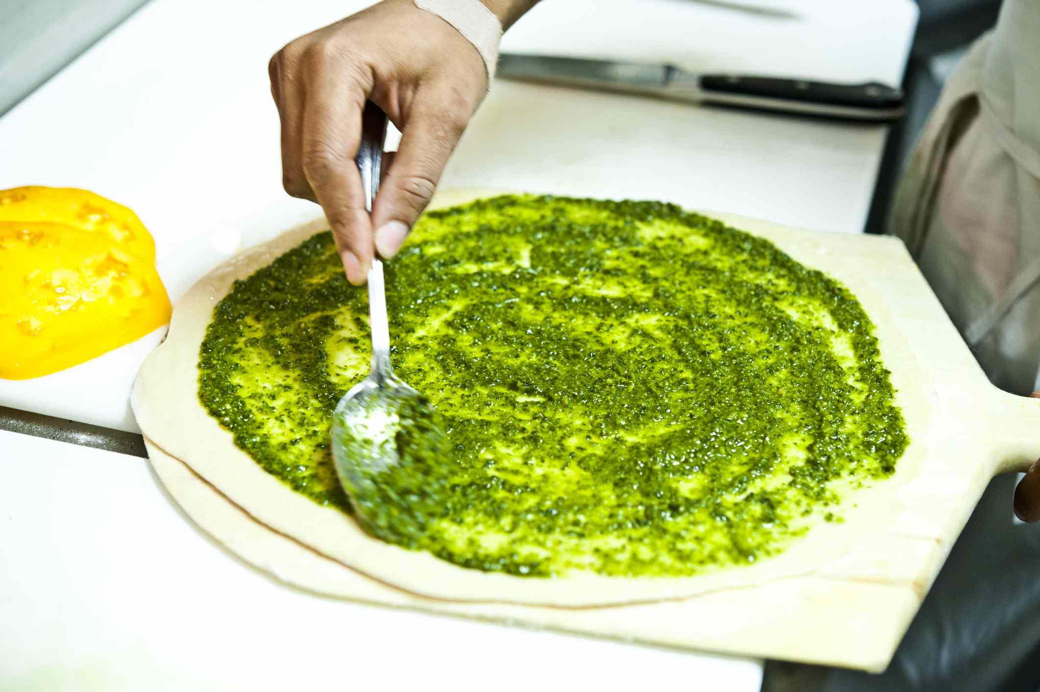 Pesto spread onto pizza dough