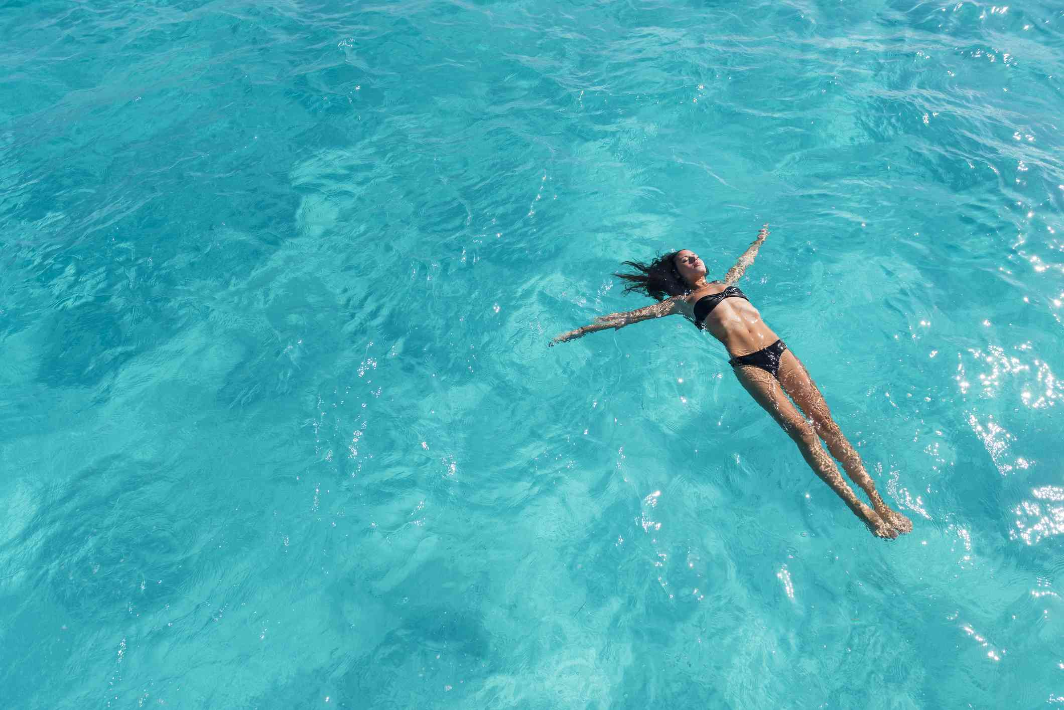 Woman floating on her back, swimming in ocean