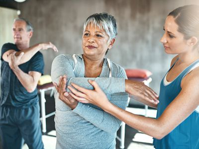 Trainer helping woman stretch her elbow in exercise class