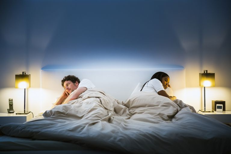 A couple in bed, turned away from one another
