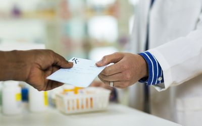 a patient handing a prescription to a pharmacist
