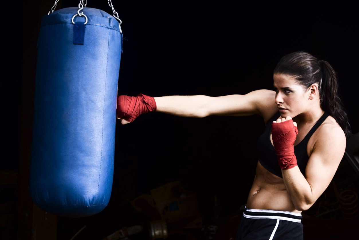 a woman hitting a heavy bag