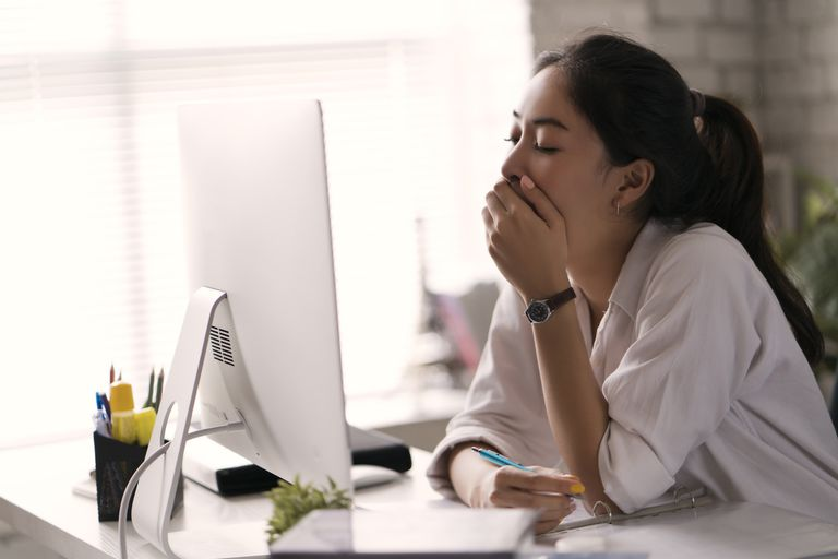 businesswoman yawning at her desk in an office