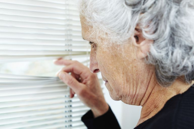 A woman with dementia paranoid at the window