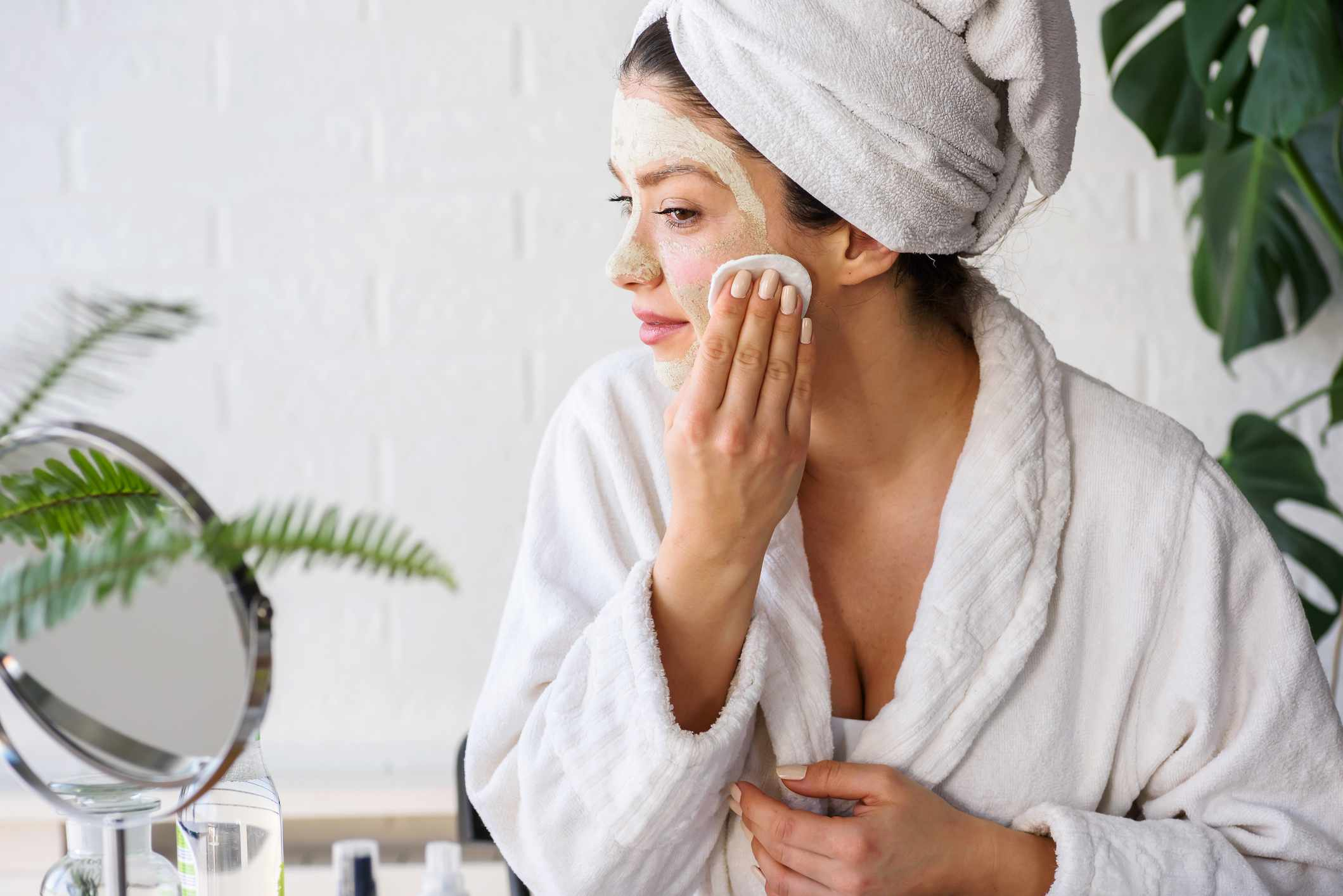 Young woman cleaning face with natural cosmetics