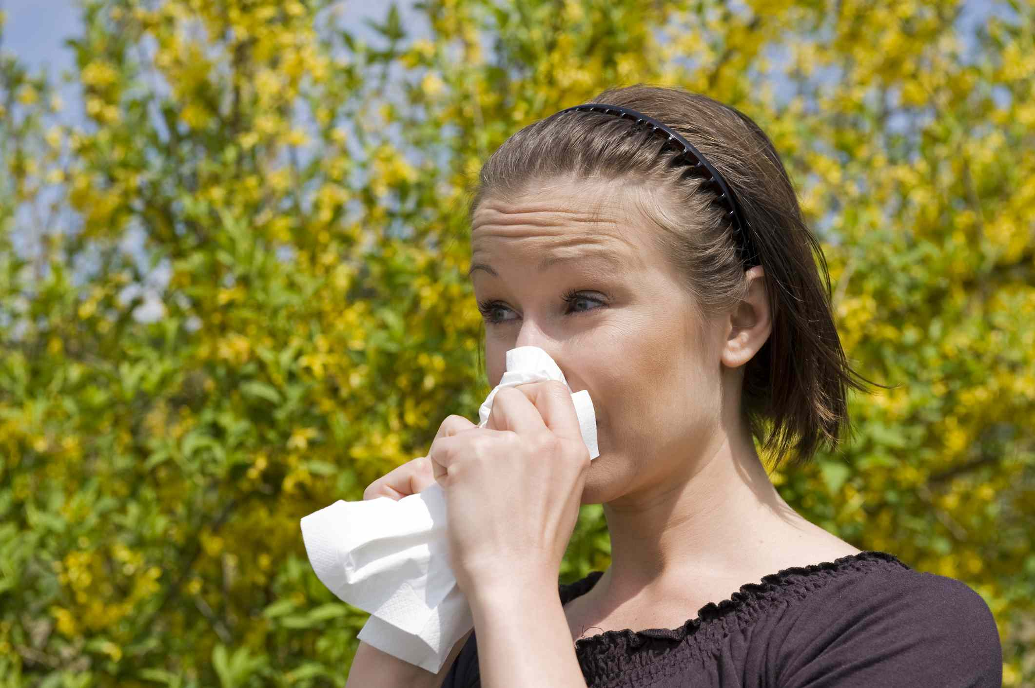 Young woman blowing nose outdoors