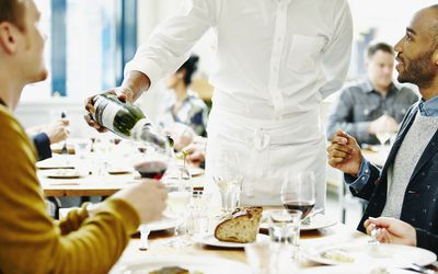 waiter serving two men at restaurant