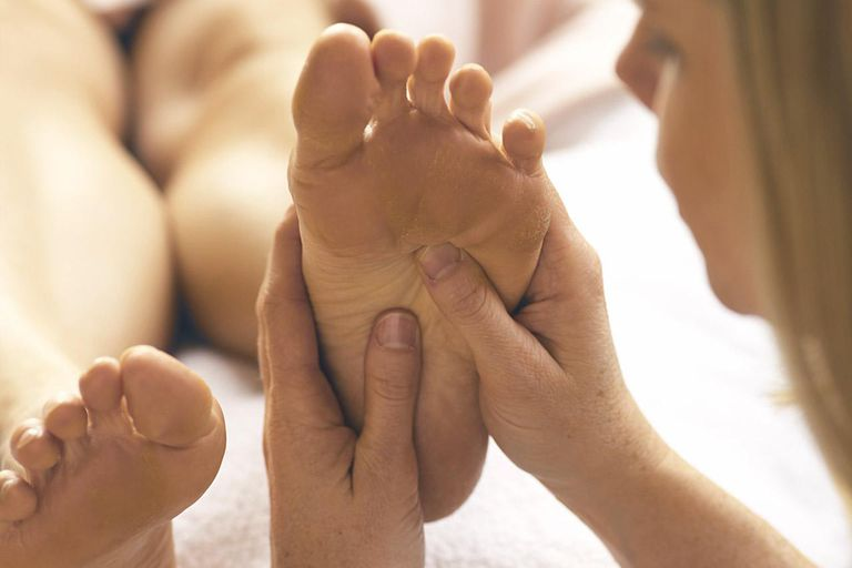 Woman getting foot massage from reflexologist (focus on foot)