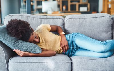 A young woman experiencing stomach pain while lying on the sofa at home.