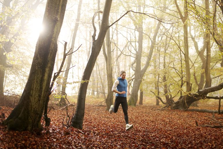 Man running through woodland in autumn